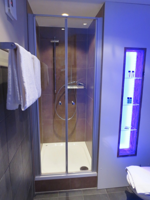 A non-plastic shower bathed in blue (or green, or red).